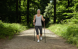 Woman using Nordic walking poles on forested trail