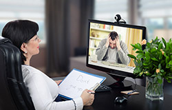 Female social worker providing counseling session to overwhelmed man using video-conferencing