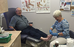 Female practitioner providing foot care to male client