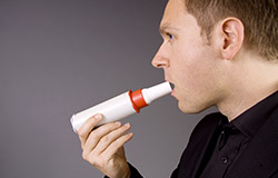 An adult male using an inhaler