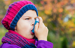 A young child using an inhaler