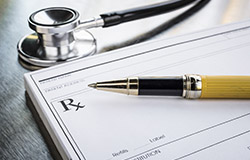 A stethoscope, pen and prescription pad sitting on a table