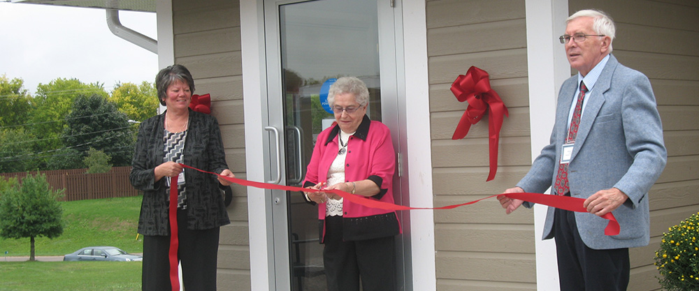 3 people cutting the ribbon at the expansion re-opening of the Beachburg site